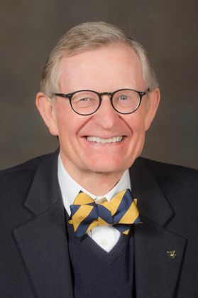 Photo of a smiling man wearing glasses and a gold and blue bowtie